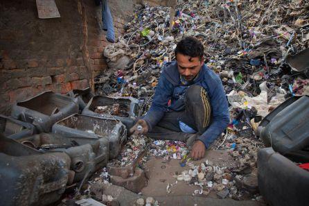 En Nueva Delhi (India) un trabajador recoge a mano pequeñas piezas de plástico para su posterior reciclaje.