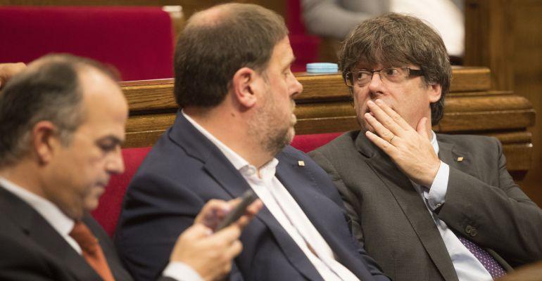 El presidente de la Generalitat, Carles Puigdemont (d), junto al vicepresidente Oriol Junqueras (c), y el conseller de la Presidencia y portavoz del gobierno catalán, Jordi Turull (i).