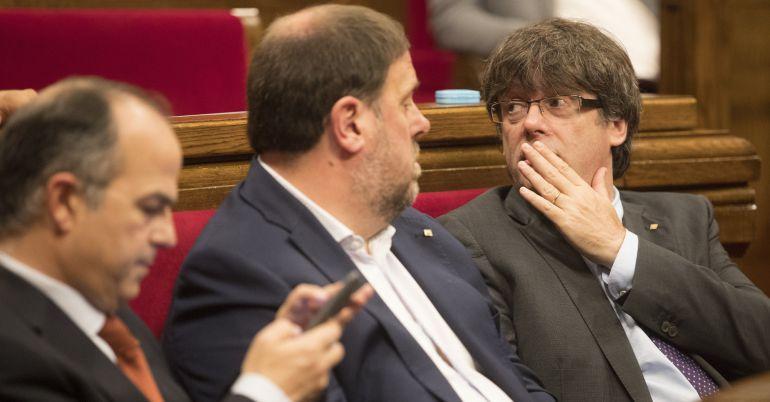 El presidente de la Generalitat, Carles Puigdemont (d), junto al vicepresidente Oriol Junqueras (c), y el conseller de la Presidencia y portavoz del gobierno catalán, Jordi Turull (i)