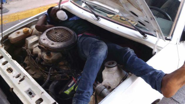 Persona hacinada en el motor de un coche