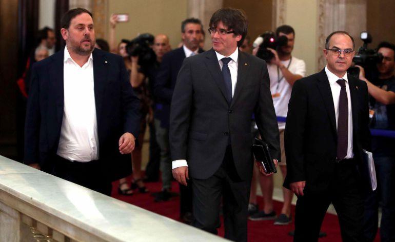 El presidente de la Generalitat, Carles Puigdemont (c), junto al vicepresidente y conseller de Economía, Oriol Junqueras (i), y el conseller de la Presidencia, Jordi Turull