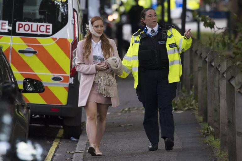Una agente de policía escolta a una herida en los alrededores de la estación de metro Parsons Green en Londres (Reino Unido).