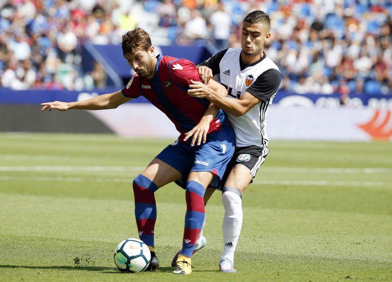 El centrocampista del Levante, José Gómez Campaña, controla la pelota ante el centrocampista del Valencia, Andreas Pereira.