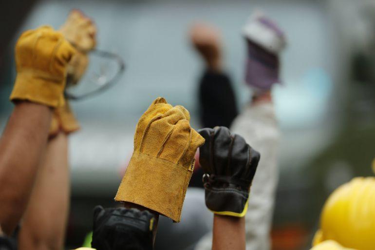 Brigadas de rescatistas y voluntarios levantan sus manos para pedir silencio absoluto mientras continúan escarbando de forma manual en las ruinas de una escuela