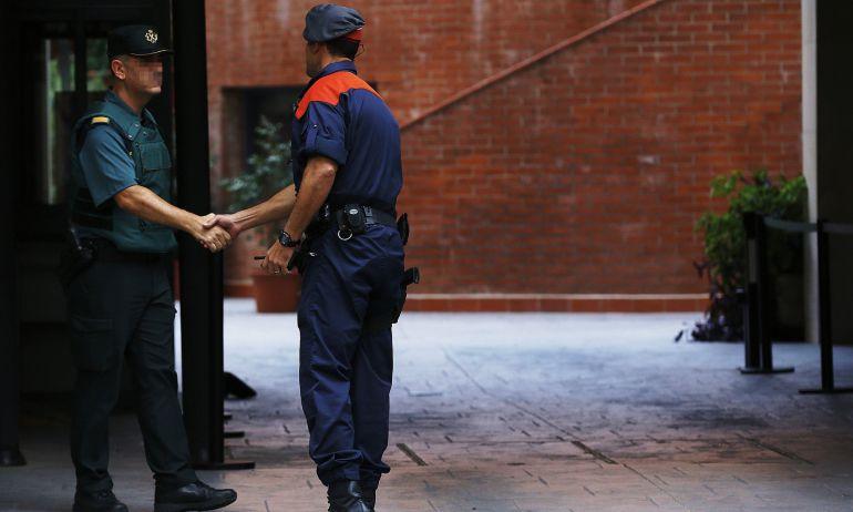Un mosso d'esquadra saluda a un guardia civil en la entrada de la caserna de Travessera de Gracia, en Barcelona, donde permanecían los detenidos de la operación Anubis.