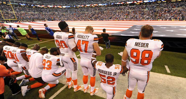 Algunos de los jugadores de los Cleveland Browns hincan la rodilla en el suelo mientras suena el himno de Estados Unidos.