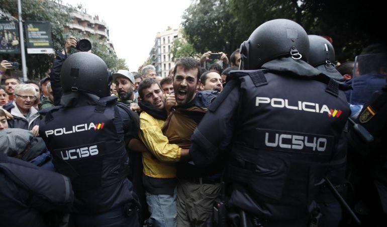 Agentes antidisturbios de la Policía Nacional forman un cordón de seguridad frente al colegio Ramón Llull de Barcelona.