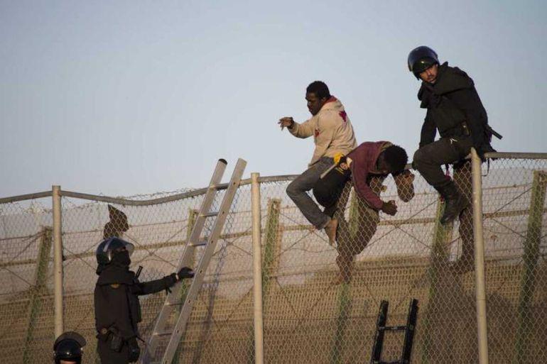 Antidisturbios españoles bajan a inmigrantes encaramados a la valla de Melilla