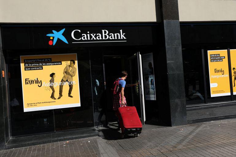 A hombre entra con una maleta en una oficina de Caixabank en Barcelona