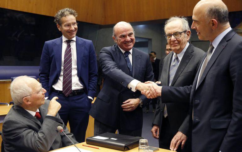 El ministro español de Economía, Luis de Guindos (c), estrecha la mano del comisario europeo de Asuntos Económicos y Financieros, Pierre Moscovici (d), en presencia del ministro de Finanzas alemán, Wolfgang Schäuble (i), el presidente del Eurogrupo, Jeroen Dijsselbloem
