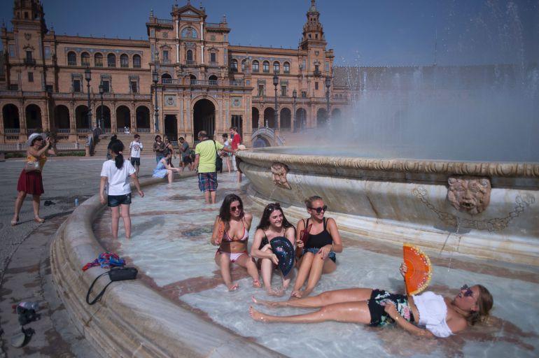 Un grupo de chicas se refresca en la fuente de la plaza de España de Sevilla el 12 de julio de 2017.