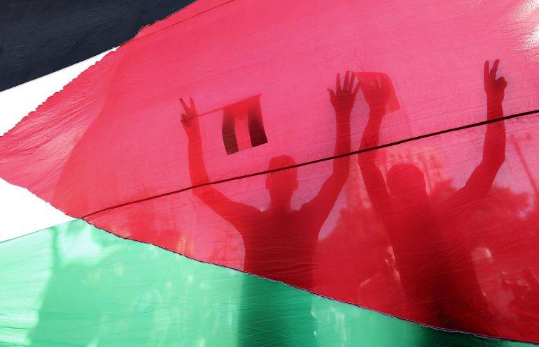 Palestinos ondean banderas de Palestina y Egipto durante una celebración tras el acuerdo entre el movimiento islamista Hamás y el partido nacionalista Al Fatah, en Gaza