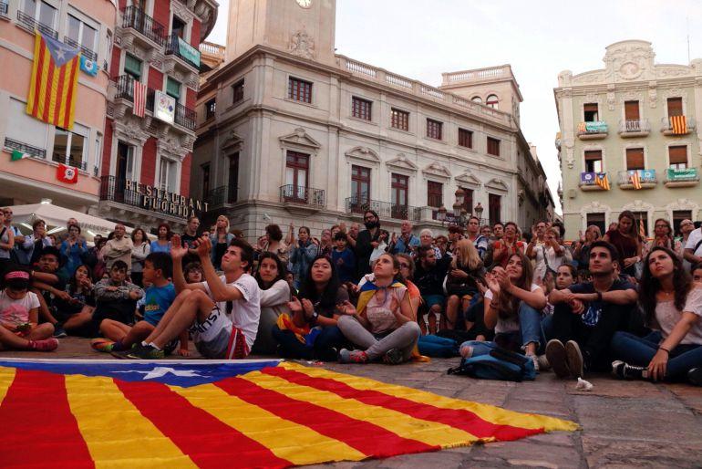 Jóvenes y niños siguiendo la declaración de Puigdemont en la plaza de Reus