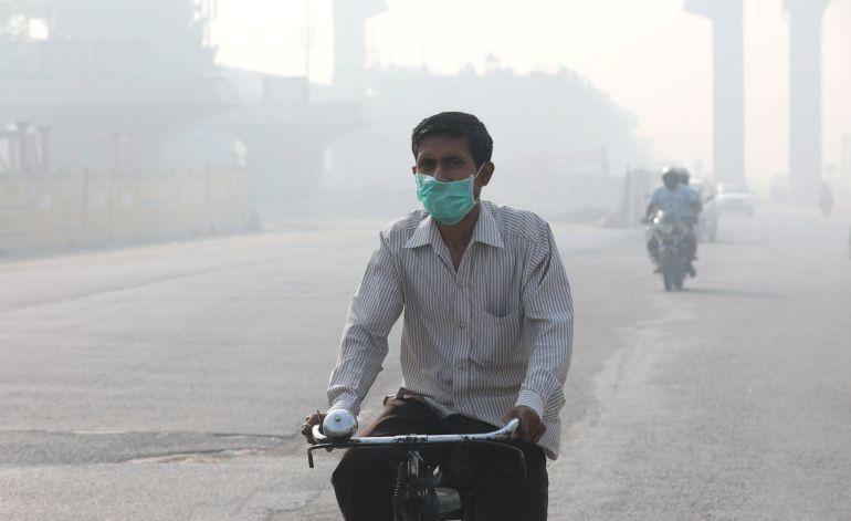 Un hombre utiliza mascarilla mientras circula en bicicleta por Nueva Delhi (India)  a causa de la contaminación provocada por el tráfico y la quema de rastrojos.