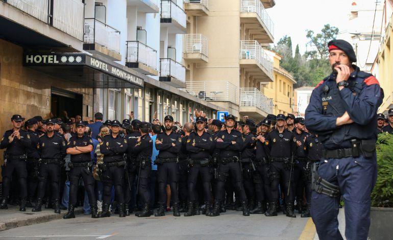 Un mosso y un grupo de policías nacionales, frente a un hotel de Pineda de Mar.