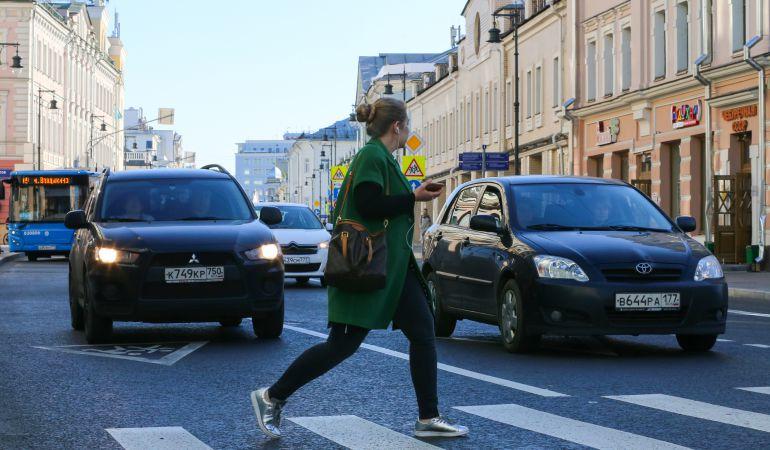 Una mujer cruza la carretera con el teléfono móvil en su mano.