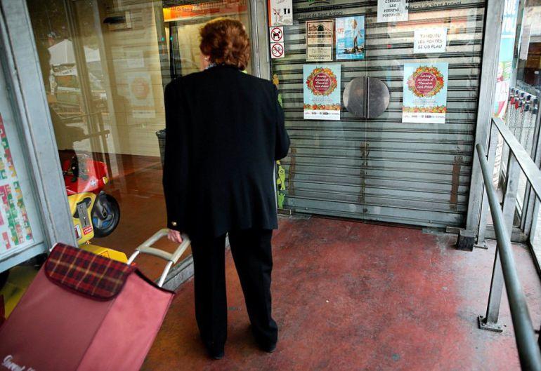 Una mujer ante las puertas del Mercado de Sant Antoni, cerrado por la huelga general del 3 de octubre en Cataluña