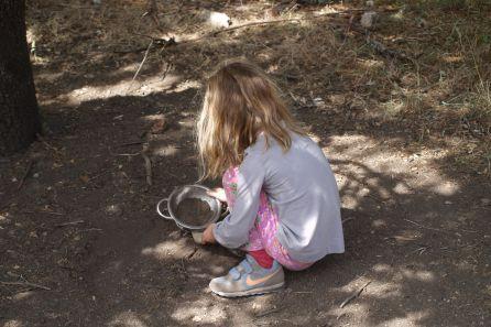 Una niña juega con el barro.