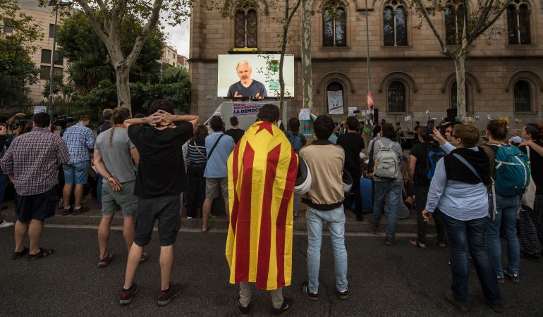 Assange habla frente al estudiantes catalanes a través de una videoconferencia.