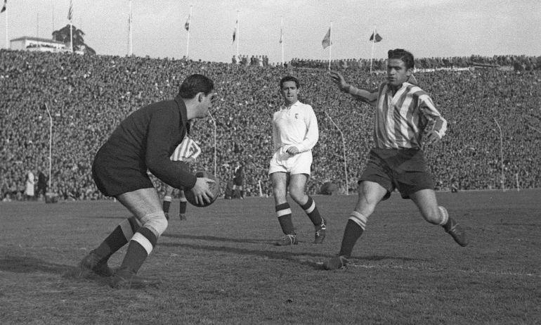 El jugador del Atlético de Madrid Farías intenta llegar a un balón que coge en sus manos el meta del Real Madrid Bañón, durante un partido de Liga disputado en el estadio Metropolitano en 1949.