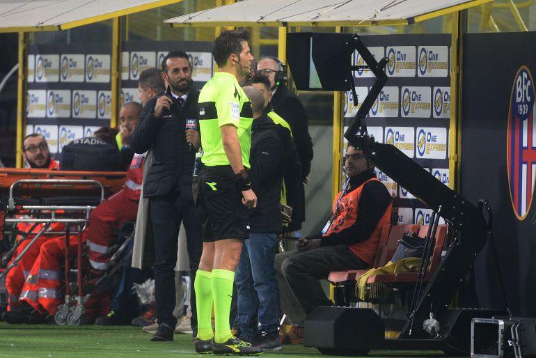 Un árbitro mira a una pantalla durante un partido en el Calcio