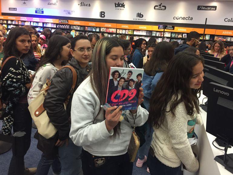 Jóvenes hacen cola frente a las cajas de la editorial Penguin Random House con el libro de CD9 en las manos.