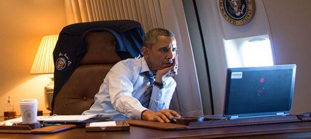 Obama consulta su ordenador portátil.