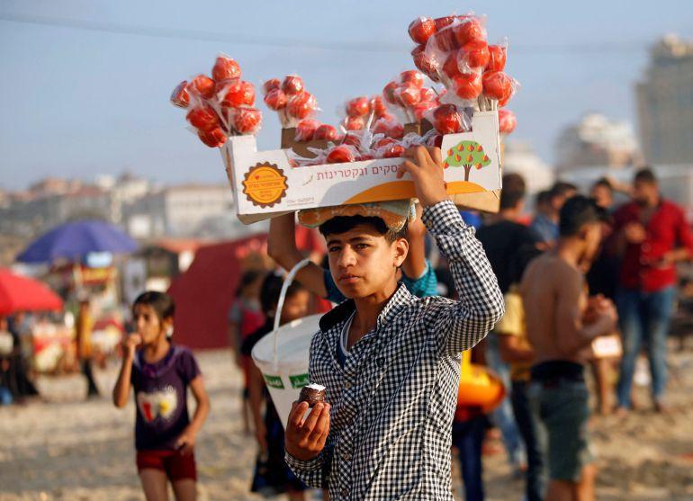 Un chico vende dulces en una playa de la franja.