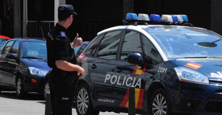 Un Policía Nacional frente a uno de los vehículos del cuerpo.