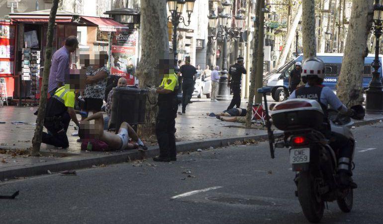 Efectivos policiales atienden a una de las víctimas de un atropello masivo de una furgoneta que ha arrollado a varias personas que paseaban por las Ramblas de Barcelona.