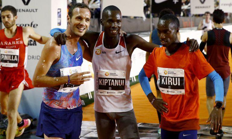 El keniano Eric Kiptanui (centro) posa junto a su compatriota Amos Kirui (derecha) y al español Toni Abadía (izquierda) tras lograr la primera, segunda y tercera posición en la San Silvestre Vallecana.