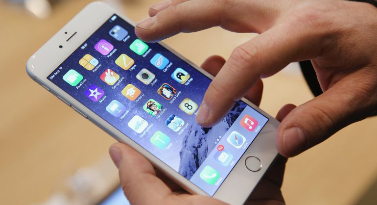 Un hombre interactua con un iPhone 6.