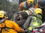 Emergency personnel carry a woman rescued from a collapsed house after a mudslide in Montecito, California, U.S. January 9, 2018. Kenneth Song/Santa Barbara News-Press via REUTERS ATTENTION EDITORS - THIS IMAGE WAS PROVIDED BY A THIRD PARTY. MANDATORY CREDIT. NO RESALES. NO ARCHIVES. TPX IMAGES OF THE DAY
