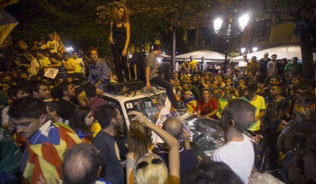 Gente subida encima de un coche destrozado de la Guardia Civil