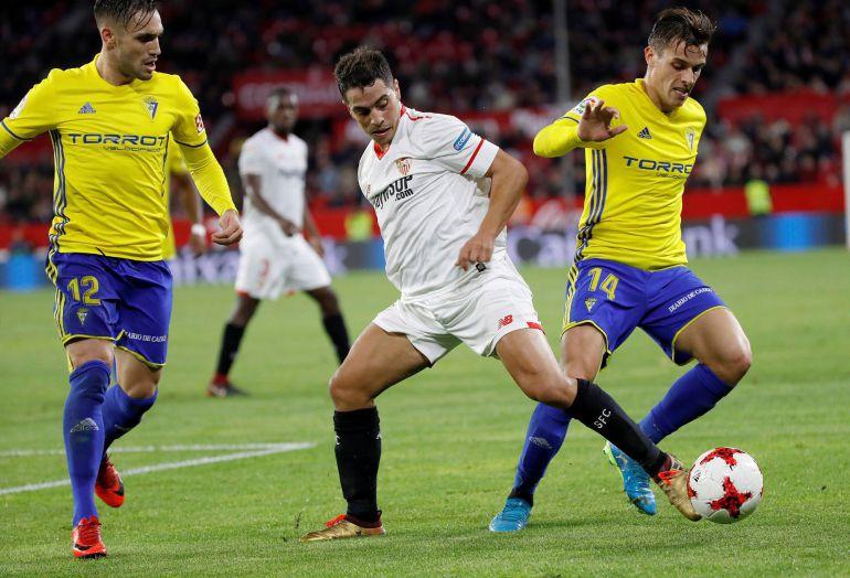 """El delantero francés del Sevilla, Wissam Ben Yedder pelea un balón con los jugadores del Cádiz """"Rober"""" y Brian Oliván."""