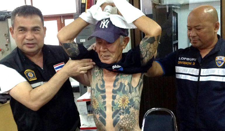 El exjefe de un clan de la Yakuza japonesa y sospechoso de asesinato Shigeharu Shirai (C) es examinado por unos agentes de la policía en una comisaría tras ser arrestado en la provincia de Lopburi (Tailandia).