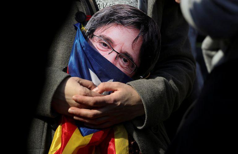 Un manifestante con una careta de Carles Puigdemont durante un acto en Barcelona