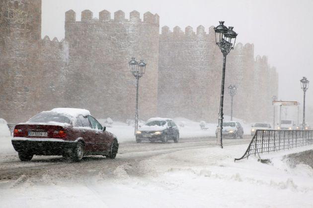 Varios vehículos circulan por una carretera próxima a la muralla de Ávila.