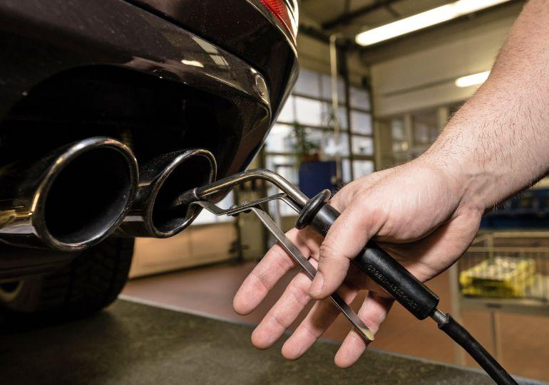 Un técnico que inspecciona el tubo de escape de un vehículo.