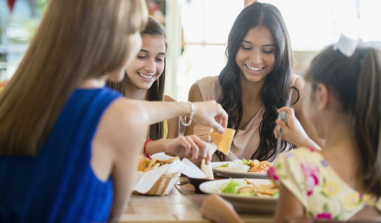 Un grupo de jóvenes comiendo nachos.