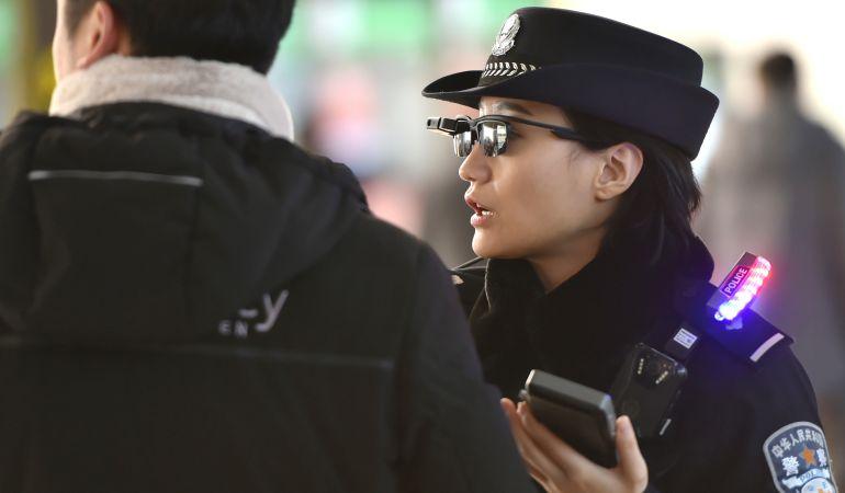 Una agente comprueba los datos de un viajero.