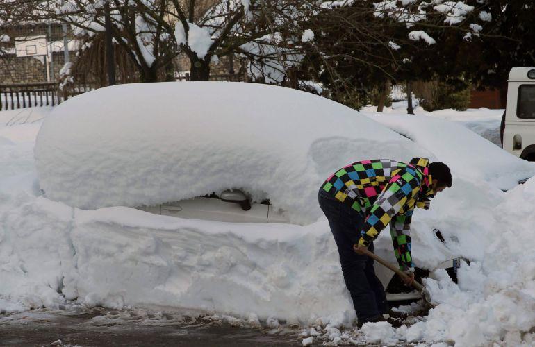 Un vecino del pueblo de Felechosa, perteneciente al Concejo de Aller, retirando nieve de un vehículo.