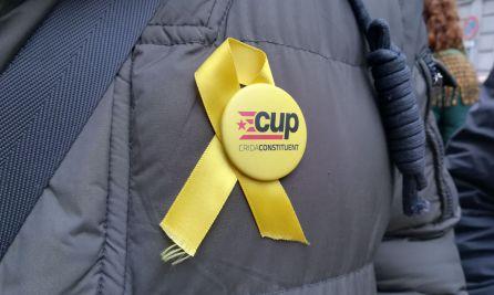 Un hombre con una chapa de la CUP y un lazo amarillo en el abrigo