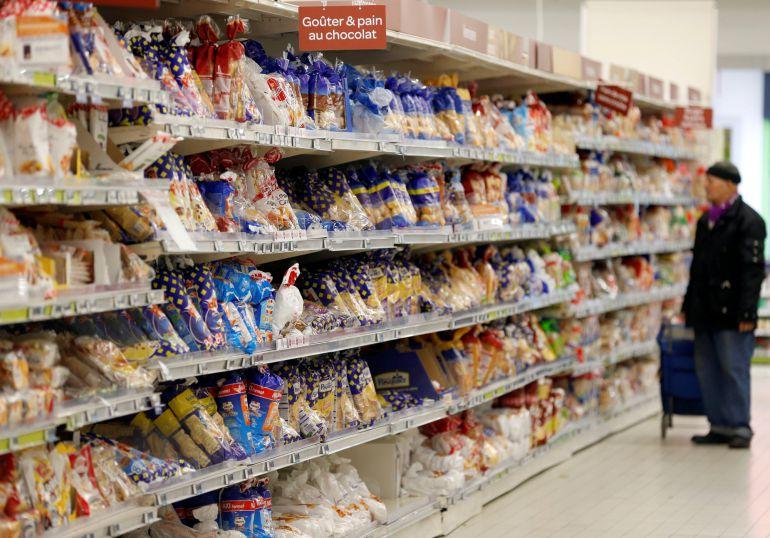 Un hombre busca alimentos ultraprocesados en un supermercado de París.