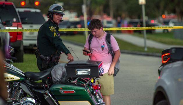 Un estudiante observa su teléfono móvil junto a un policía tras el tiroteo.