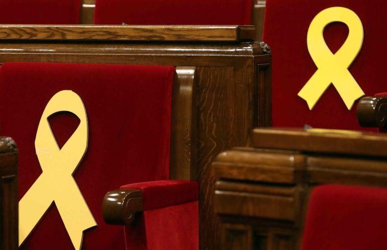 Lazos amarillos en los escaños de los diputados presos, Jordi Sánchez y Oriol Junqueras, en el Parlament