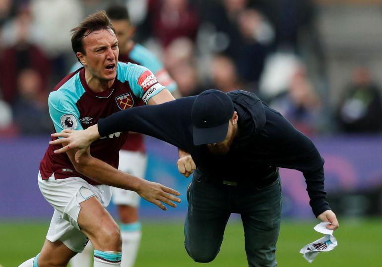 Mark Noble, del West Ham, intenta detener a uno de los espectadores que saltó al césped en el partido ante el Burnley.