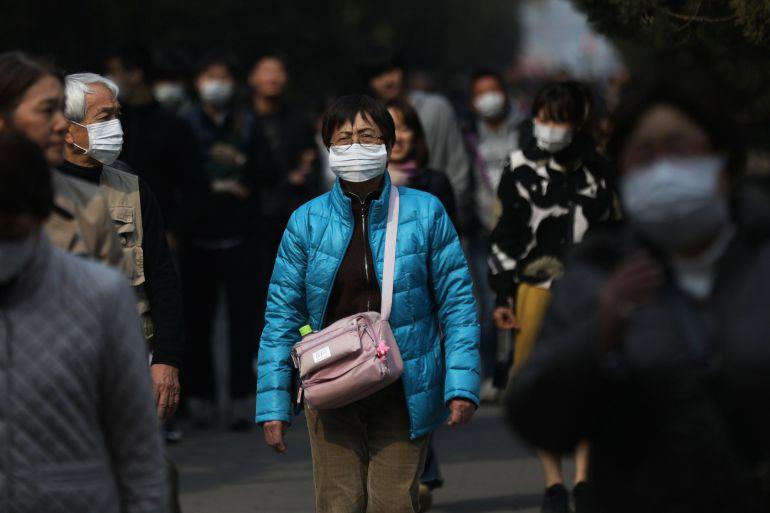 Varios turistas se protegen con mascarillas mientras visitan Pekín (China) porque las autoridades de esta ciudad han emitido una alerta naranja, la segunda más alta, debido a los altos niveles de contaminación del aire.
