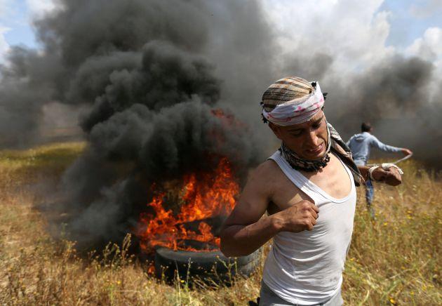 Un palestino corre durante los enfrentamientos con soldados de Israel