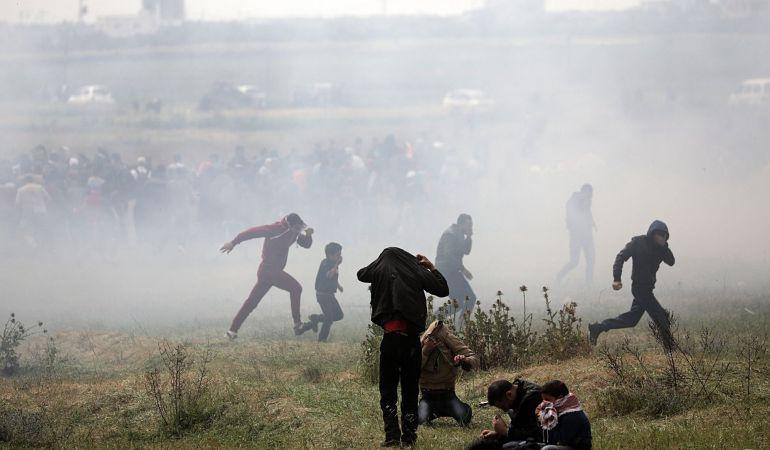 Varios palestinos huyen de gases lacrimógenos durante los enfrentamientos con soldados israelíes en el este de Beit Hanun, norte de la Franja de Gaza.